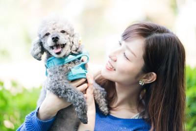 犬を抱き上げる女性