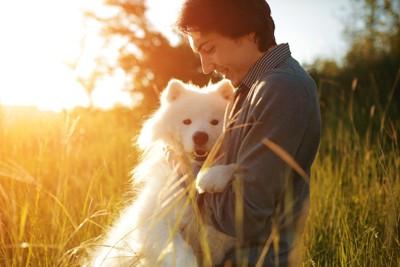 夕暮れに抱き合う人と犬