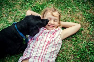 寝転がる子どもの顔を舐める犬