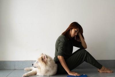 悩む女性に寄り添う犬
