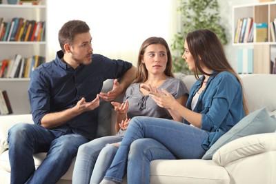 ソファーで話し合う家族