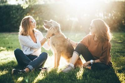芝生に座る二人の女性に可愛がられている犬