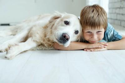 寄り添って寝そべる少年と犬