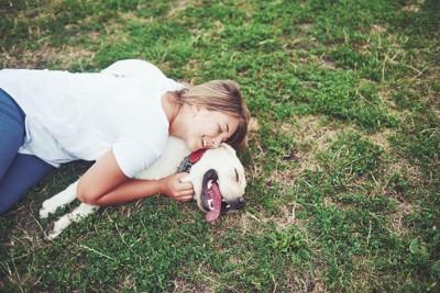 芝生の上に寝転ぶ犬に抱きつく女性