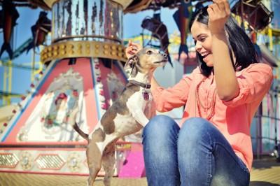 遊園地の階段に座る女性と犬