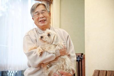 犬を抱く年配の男性