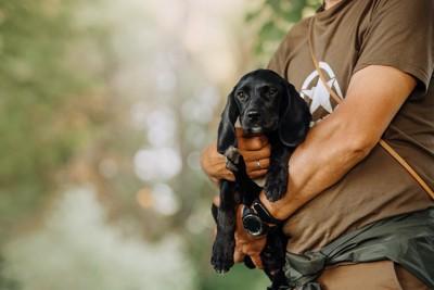 黒い子犬を抱っこして散歩する人