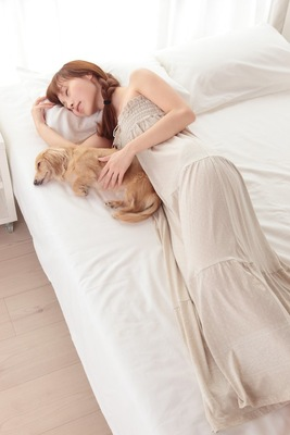 ベッドで愛犬と一緒に寝る女性