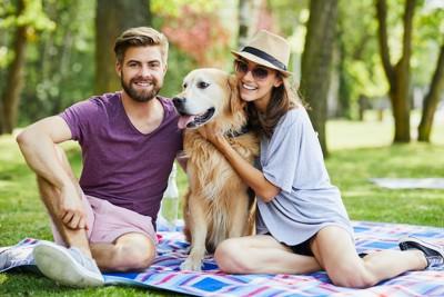 犬と一緒にピクニックを楽しむカップル