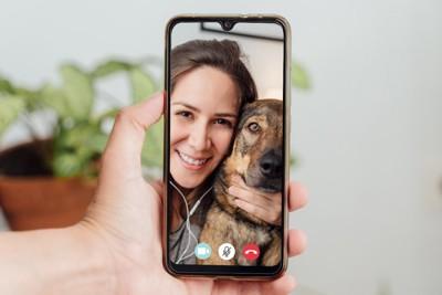 犬と一緒にビデオ通話する女性