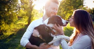 犬を抱く男性とキスをする女性