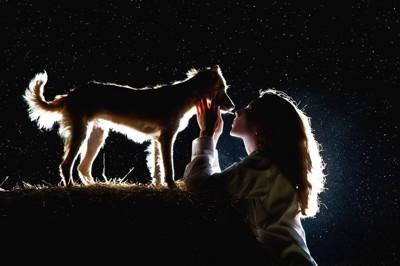 暗闇で見つめ合う女性と犬