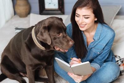 メモ帳をつける女性と犬