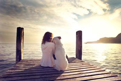 桟橋で寄り添って座る女性と犬