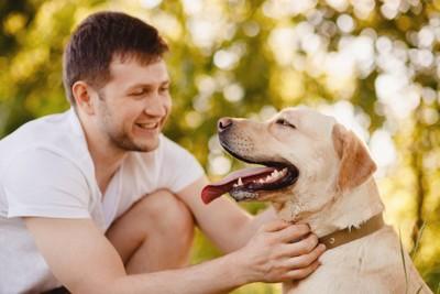 しゃがんで触れ合う人と犬