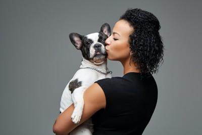 犬を抱き上げてキスをする女性