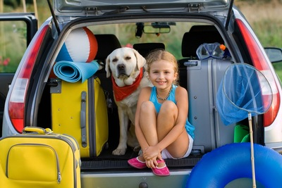 車のトランクに座る少女と犬