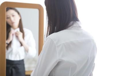 鏡の前で出かける準備をする女性