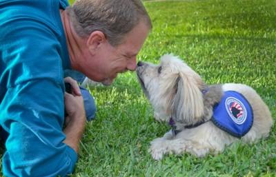 男性とサービスドッグのベストを着た小型犬