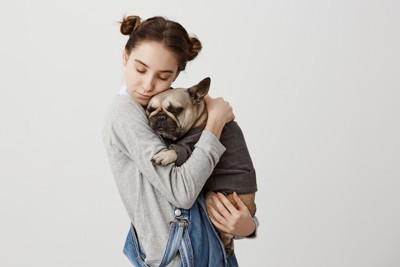 飼い主さんに抱きしめられるフレンチブルドッグ