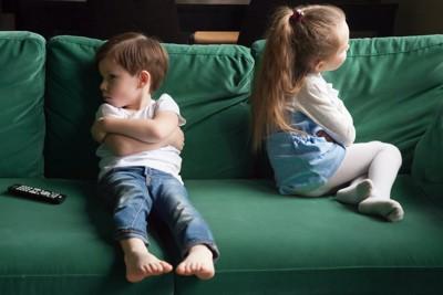 ソファーで喧嘩している男女の子ども