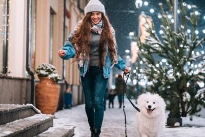 女性と冬の街を散歩している犬