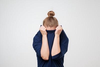 服に顔を埋める女性