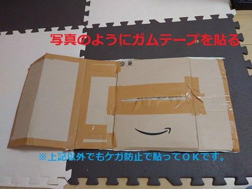 開いた段ボール ガムテープで貼っている 赤文字と水色文字