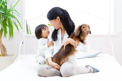 犬を抱いたお母さんに甘える子供