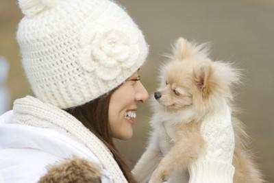 白いニット帽をかぶった女性と犬