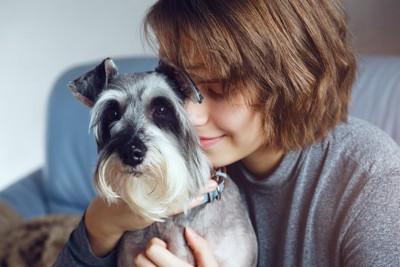 寄り添う犬に顔をくっつける女性