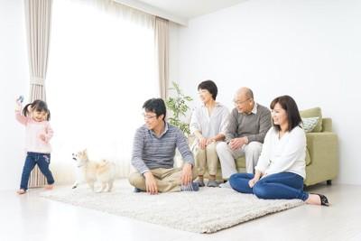 リビングで子供と遊ぶ犬を見守る家族