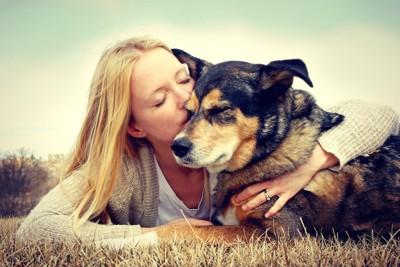 犬を抱き寄せてキスをする女性