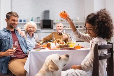 食卓を囲む家族と犬