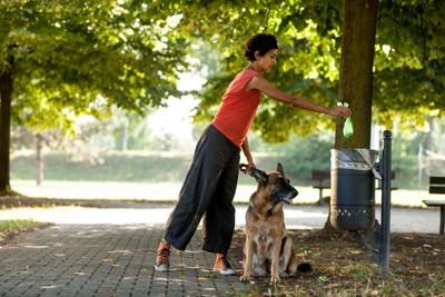 犬のウンチをゴミ箱に捨てる女性
