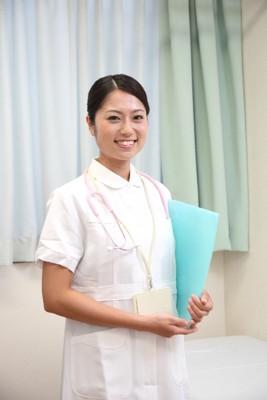女性看護士 髪を一つにまとめている カルテを持ち立っている