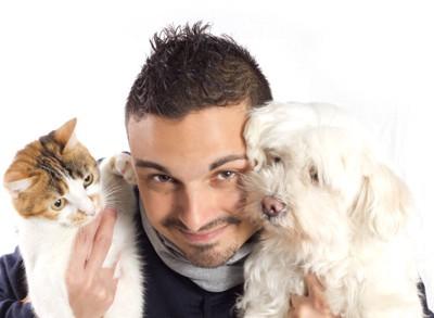 猫と犬を抱いた男性