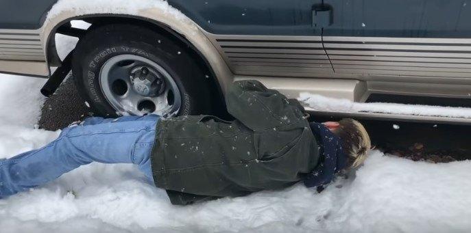 雪の上に寝そべって車の下をのぞく人