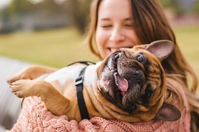 女性に抱きかかえられてご機嫌な犬