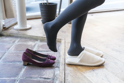 玄関で靴を脱いでスリッパに履き替える女性