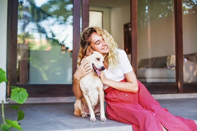 犬と寄り添う赤いスカートの金髪女性
