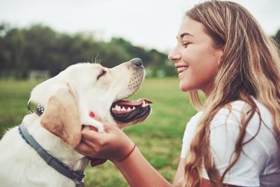 笑顔で犬と見つめ合う女性