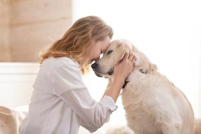 おでこを付け合う女性と犬