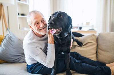 高齢の男性と黒い犬