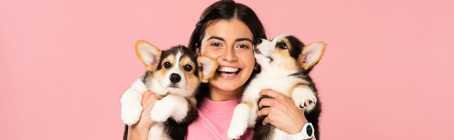 両手に二匹の子犬を抱えて笑う少女