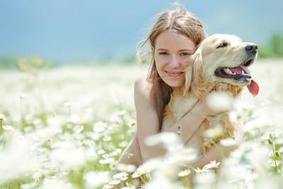 花畑で犬を抱く女性