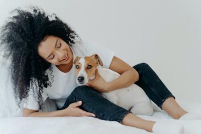 座っている女性の足の間に入ってくっつく犬