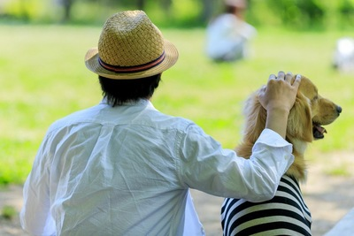 ゴールデンレトリバーと麦わら帽子の男性の写真