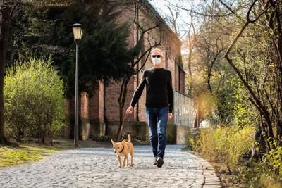 散歩するマスクの男性と犬
