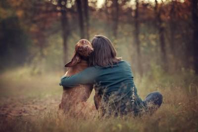 飼い主の女性に抱かれてこちらを振り返る犬